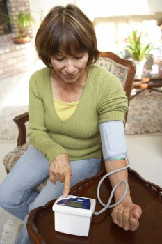 Middle aged woman taking a blood pressure reading at home with a personal blood pressure monitor.